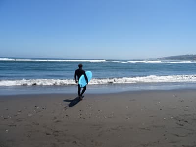 Surfer mit Surfboard in Chile.