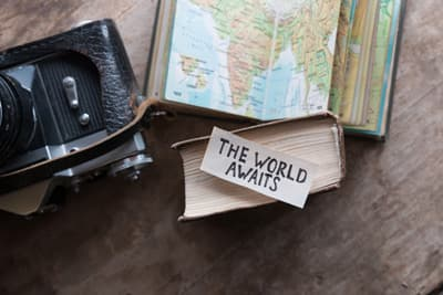 "Karte, Fotoapparat und ein Schild ""The World Awaits"""
